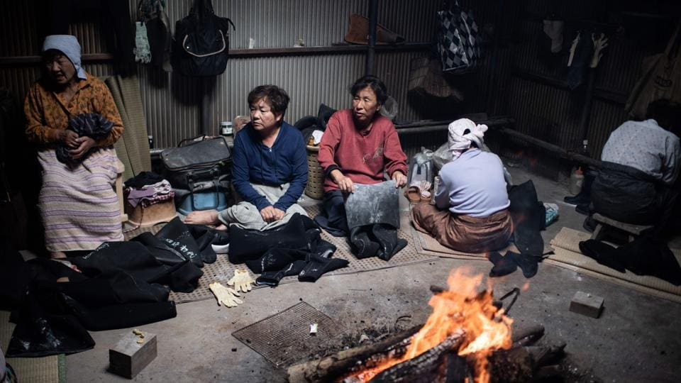 "The women, some bent over with age, acknowledge the work is poorly paid and dangerous. ""Of course I would love the kids to take over, but I know that being an ama diver is a difficult job and I don't recommend it, even to my own children,"" says Koguchi's sister Michiko Hashimoto warming herself up around a fire in a the hut where the women gather to recharge. (Martin Bureau / AFP)"