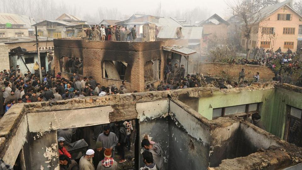 Villagers gather near a damaged house after a gunfight between militants and security forces, in Chattergam, Budgam district, central Kashmir. Lashkar-e-Taiba commander Naveed Jutt, who according to Jammu and Kashmir police was the prime accused in the killing of senior journalist Shujhaat Bukhari, and another militant were killed in the gun battle with security forces. (Waseem Andrabi / HT Photo)