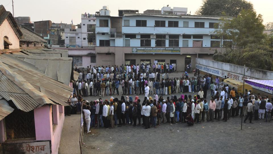 Voters stand in queues to cast their ballots for the Madhya Pradesh state assembly elections in Jabalpur on November 28.