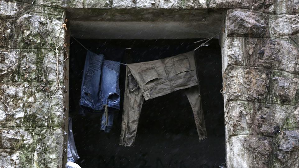 Clothes hang from a rope at a window of a shelter. Some migrants wear only worn-out shoes and no socks as they line up to receive a hot meal from aid groups helping out in the Borici camp, a former student dormitory damaged during the war. (Amel Emric / AP)