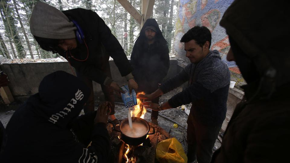 Migrants prepare food by a fire at a shelter in Bihac. Thousands of migrants from the Middle East, Africa or Asia have been flocking to northwestern Bosnia for the crossing, and many must try several times before they manage to slip past the border police. (Amel Emric / AP)