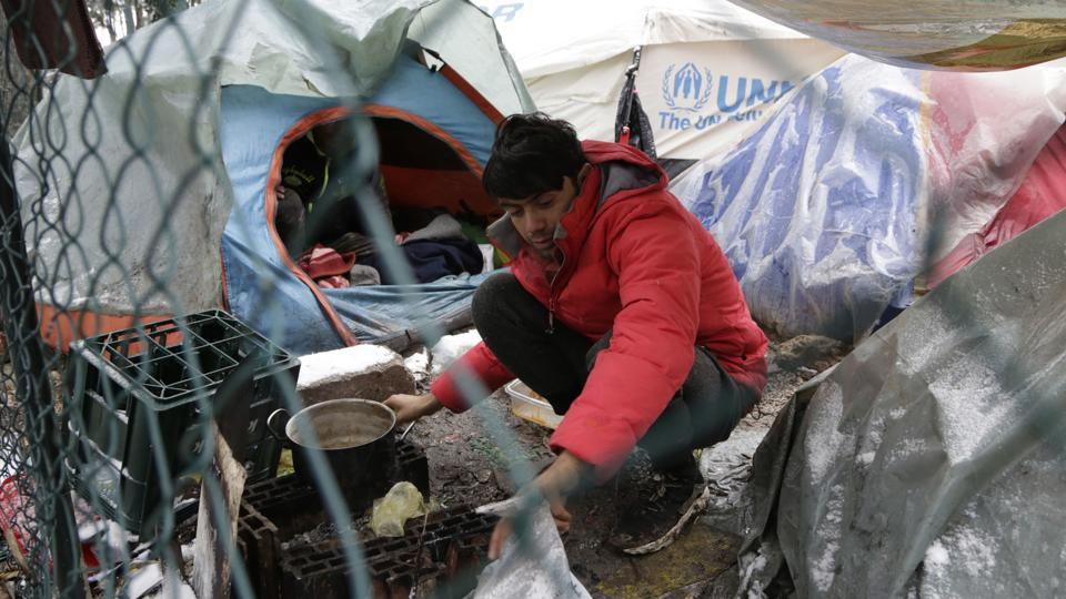 "A migrants prepares food. ""It's very difficult to survive here,"" said Feroz Han Amanazay from Afghanistan, noting that the water is cold, there is no heating and the tents are too big to warm up. (Amel Emric / AP)"