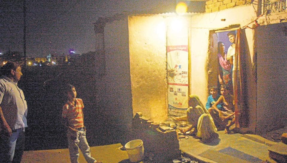 A family in the light of a bulb in a slum. Image for representation.
