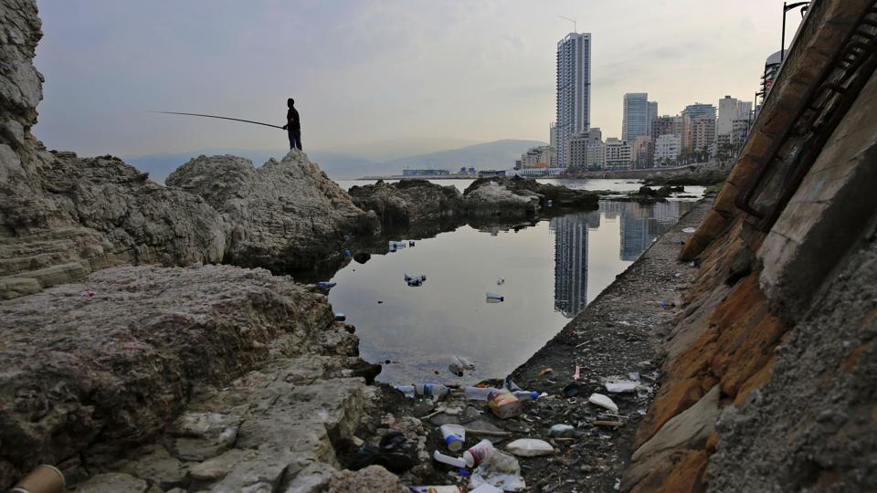 A man casts his fishing pole in the Mediterranean Sea on a rocky coastal area along the Beirut coastline. Once a source of pride, the country's Mediterranean coastline has become a source of shame for many Lebanese because of the swirling trash that pollutes its shores. (Hassan Ammar / AP)