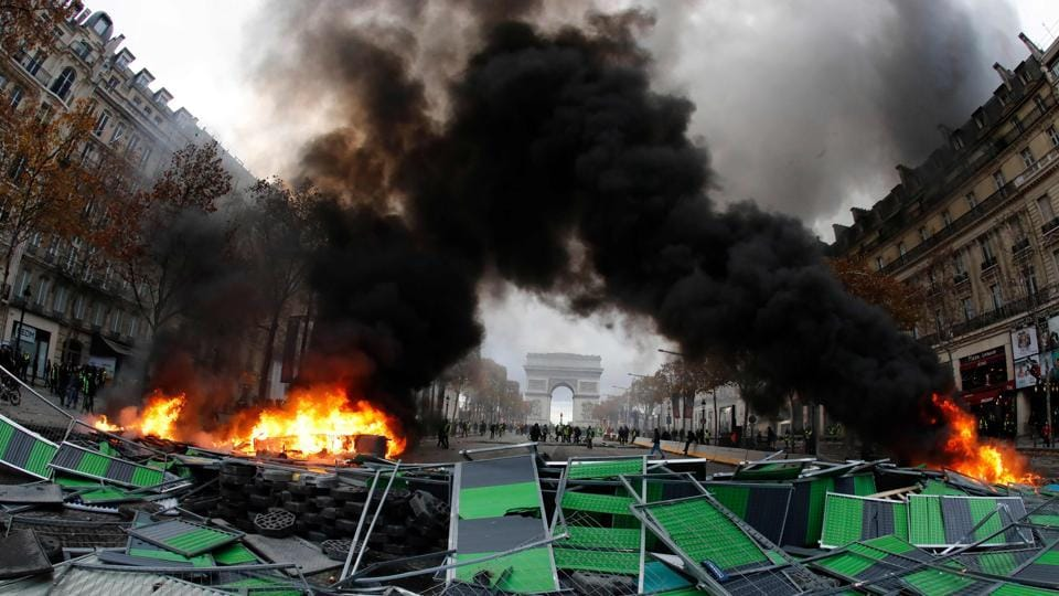 Material burns during a protest against rising oil prices and living costs by Yellow vests (Gilets jaunes) near the Arc of Triomphe on the Champs Elysees in Paris. The 'yellow vest' protesters have been demanding French President Emmanuel Macron roll back tax hikes on motor fuel. (AFP)