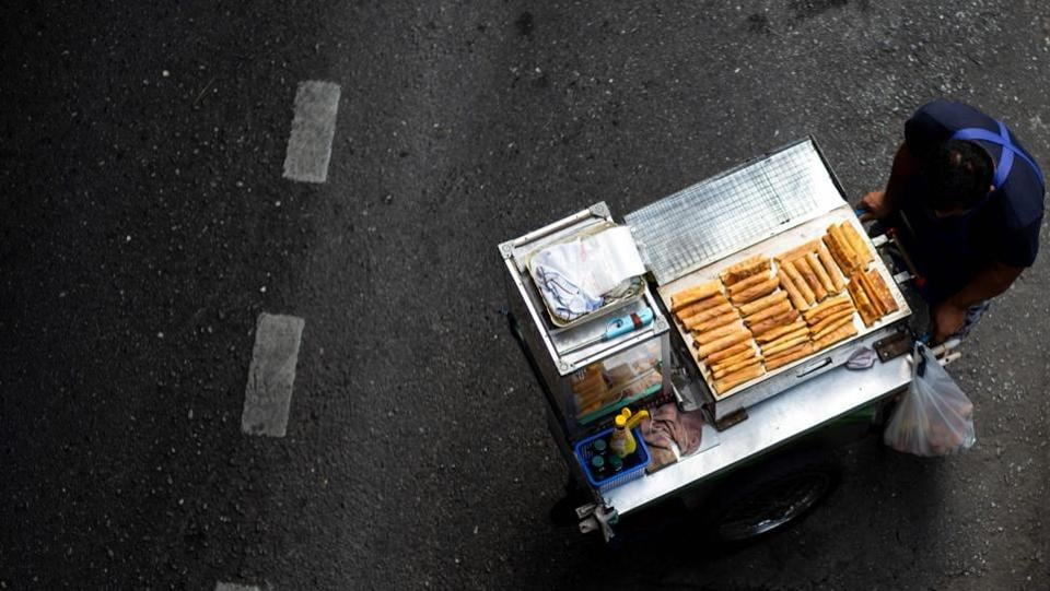 A vendor pushes his food cart looking for customers along a street in Bangkok, Thailand. (Jewel Samad / AFP)