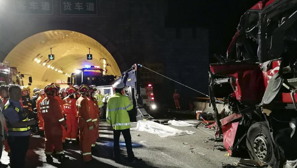 In this photo released by China's Xinhua News Agency, first responders work at the site of an accident after a coach hit the wall of the Qinling Mountains No. 1 Tunnel on the Jingkun Expressway in Ningshan County, northwestern China's Shaanxi Province in August 2017.