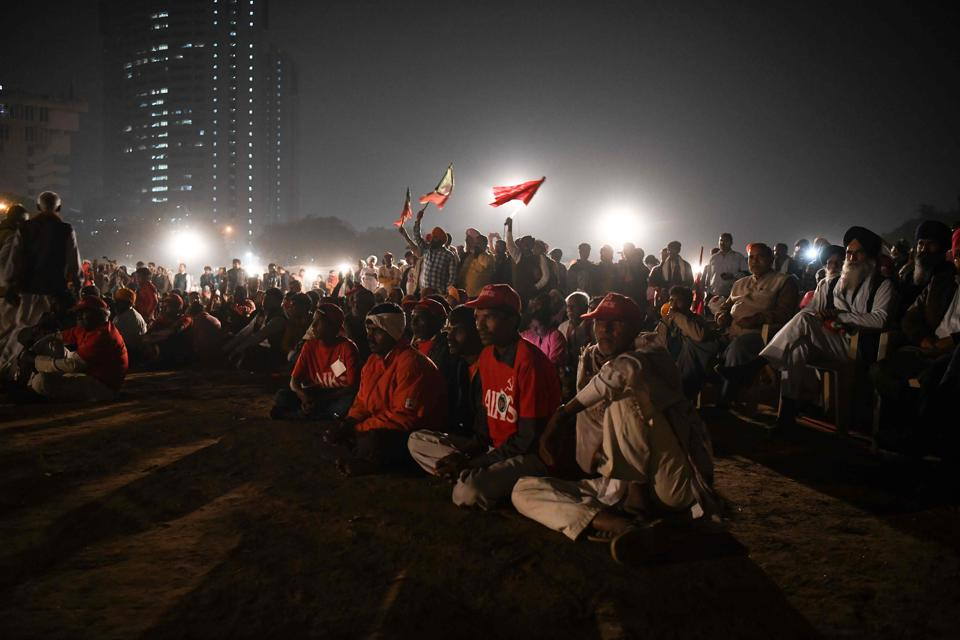 The farmers converged in the national capital on Thursday at the Ramlila maidan, known for hosting big political events over the years. The location resonated with slogans like 'Ayodhya nahi, karz maafi chahiye' as farmers wearing red caps and carrying red flags started to gather. (Chandan Khanna / AFP)