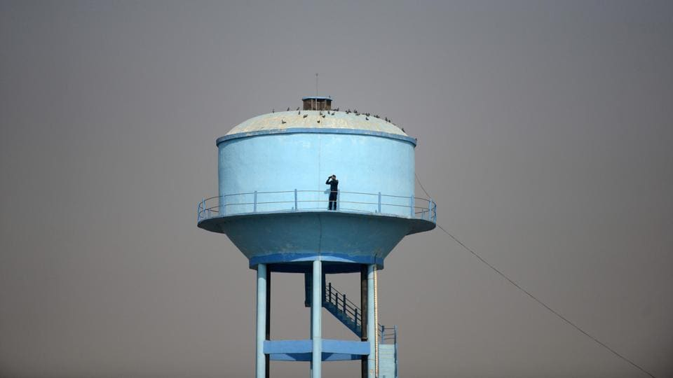 A security personnel watches from atop a water tank near the 'Dharam Sabha' Hindu congregation held to call for the construction of a grand temple of Lord Rama, in Ayodhya, Uttar Pradesh on November 25, 2018. (Sanjay Kanojia / AFP)