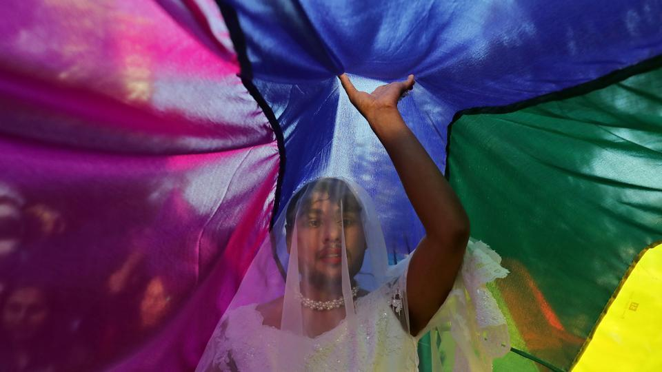 A participant touches a rainbow flag during the Queer Pride March, an event promoting gay, lesbian, bisexual and transgender rights, in New Delhi on November 25, 2018. (Anushree Fadnavis / REUTERS)