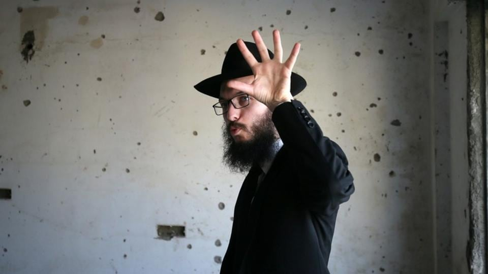 Rabbi Israel Kozlovsky gestures next to a wall riddled with bullet holes after the renaming of Nariman House as Nariman Light House, which was one of the targets of the November 26, 2008 attacks in Mumbai, Maharashtra on November 25, 2018. (Francis Mascarenhas / REUTERS)