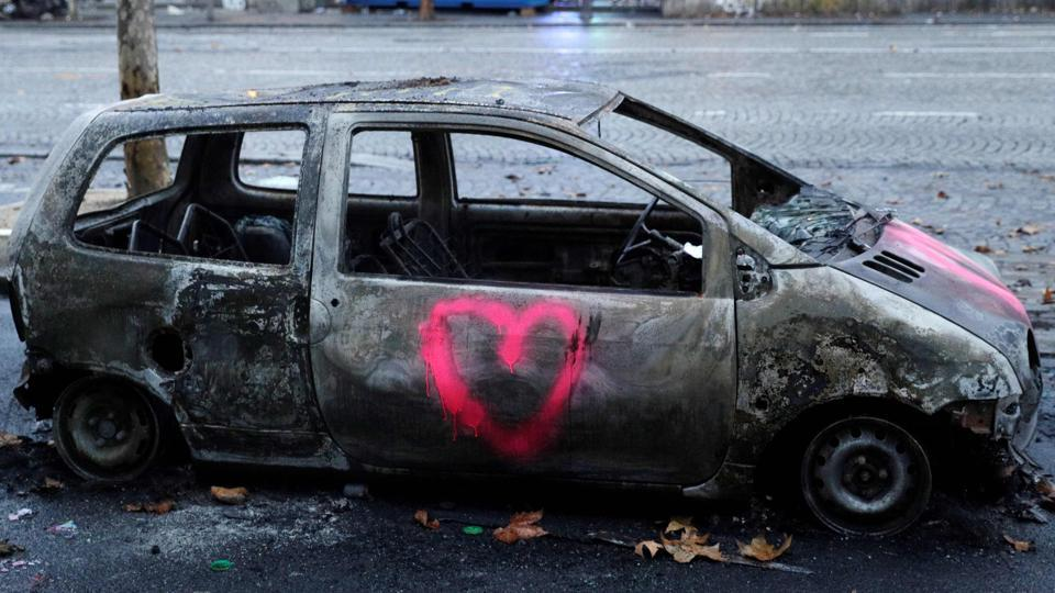 A picture shows a burned car in a street of Paris on December 2, 2018, a day after clashes during a protest of Yellow vests (Gilets jaunes) against rising oil prices and living costs.