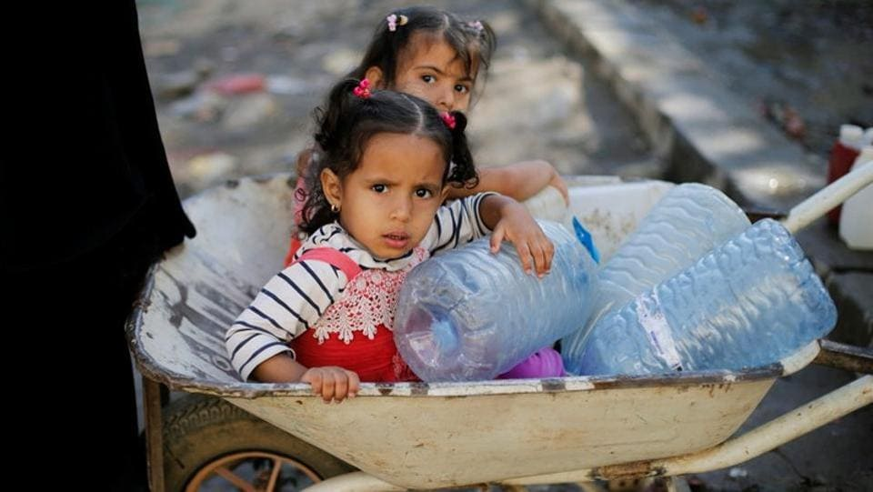 """Girls wait next to a charity tap. More than 250,000 cases of cholera have been recorded in Yemen since the beginning of 2018, with 358 associated deaths, UNICEF representative Meritxell Relano told Reuters. """"We have prevented an outbreak at the scale of 2017,"""" Relano said. """"But the risk is still there."""" (Khaled Abdullah / REUTERS)"""