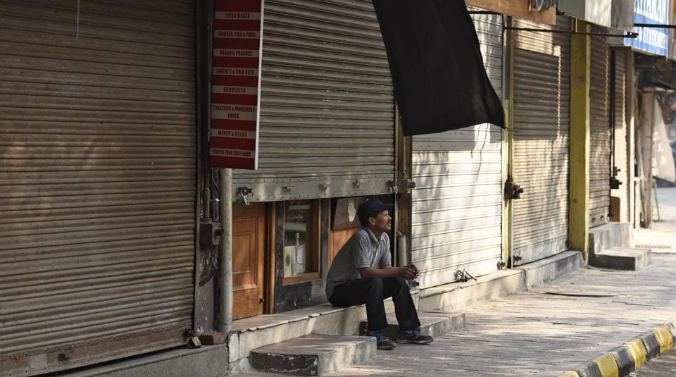 File photo of a person sitting outside a shop in the main market of Defence Colony, New Delhi.