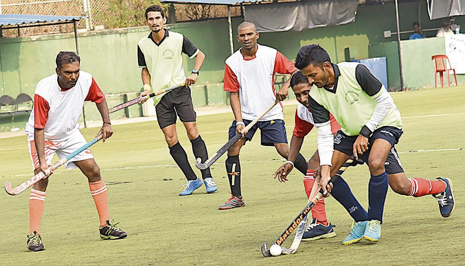 Aurangabad (red and white) in action against Jalgaon at the 115th Aga Khan cup hockey tournament at Major Dhyan Chand hockey stadium at Nehrunagar, Pimpri, on Tuesday