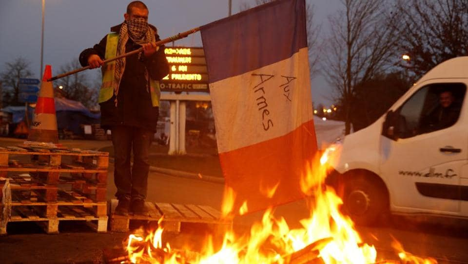 A protester wearing a yellow vest, the symbol of a French drivers' protest against higher diesel fuel prices, holds a flag near burning debris in Fontaine-Notre-Dame, France.
