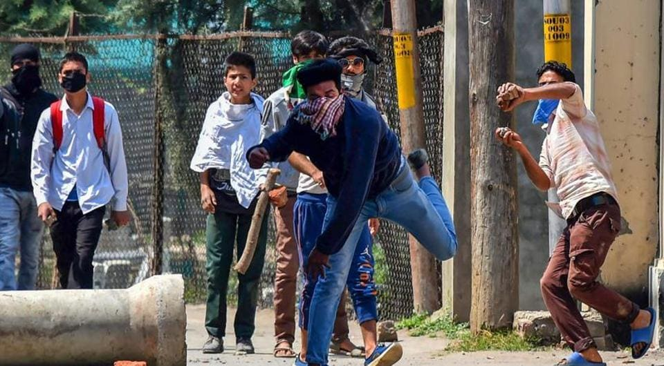 Students throw stones at the police during a protest over arrest of the student Adil when he was entering the school, at Soura on the outskirts of Srinagar on Saturday.
