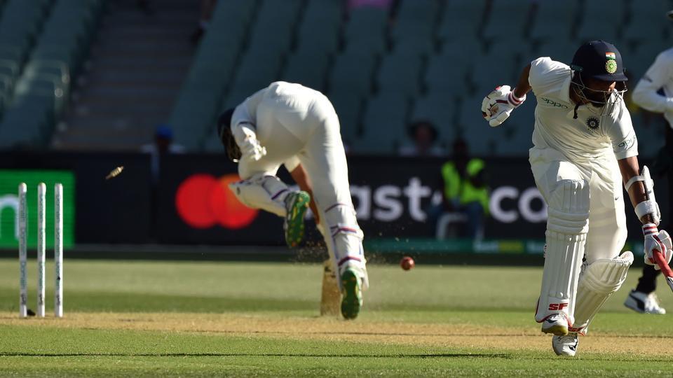India's batsman Cheteshwar Pujara (L) is run out by a direct throw from Australian fieldsman Pat Cummins.