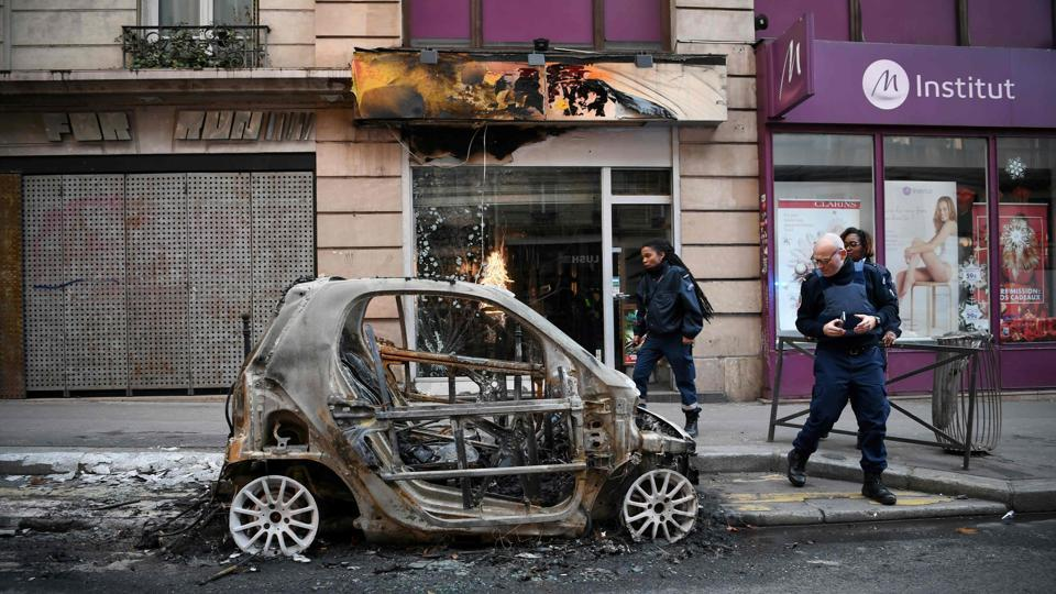 Police look at a burnt car in Beaubourg street in Paris, on December 9, 2018 a day after a 'yellow vest' protests as part of a fourth weekend of nationwide protests.