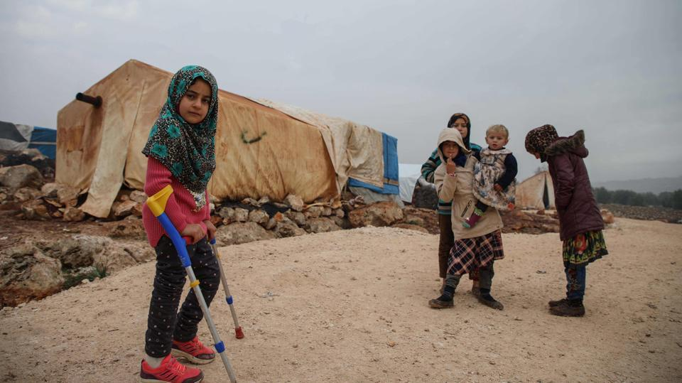 Syrian Maya Merhi stands with her friends in the Internally Displaced Persons (IDP) camp of Serjilla in northwestern Syria next to Bab al-Hawa border crossing with Turkey, on December 9, 2018. Until a few days ago, eight-year-old Merhi had to struggle around the camp on artificial limbs made of plastic tubing and tin cans. (Aaref Watad / AFP)