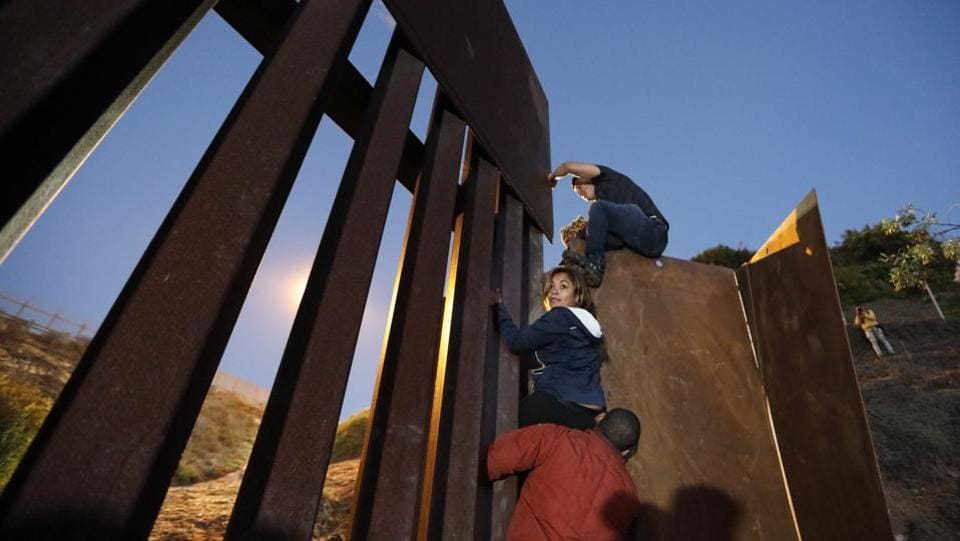 A group of young people hoisted themselves over the wall to San Ysidro, California, hoping that their ticket to a better life was finally within reach. One migrant offered a hand to help the others jumping down onto US territory. (Rebecca Blackwell / AP)
