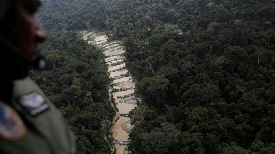 "A policeman observes an illegal gold mine. Rolla said she hopes environmental agencies will use it as a tool to help police the mines. ""The studies show that illegal mining is increasing a lot,"" Rolla said. ""I think the government needs to be more worried about giving Ibama more resources to do their job."" (Ricardo Moraes / REUTERS)"