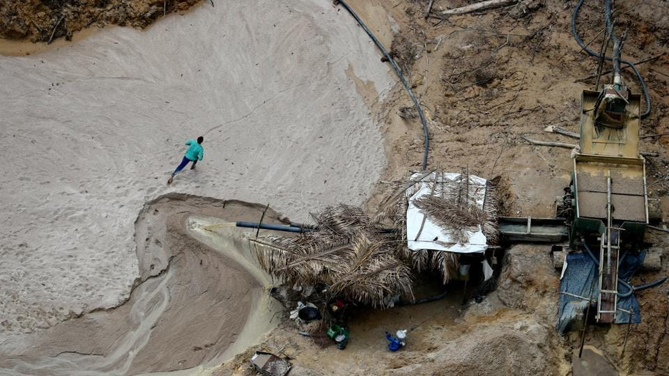 A miner runs away from an illegal cassiterite mine. As government helicopters descended along stagnant pools ravaged by miners, many fled deep into the rainforest. The operation was carried out against a handful of what are now known to be hundreds of illegal Amazon mines in Brazil that have been catalogued for the first time in a study released on Monday. (Ricardo Moraes / REUTERS)