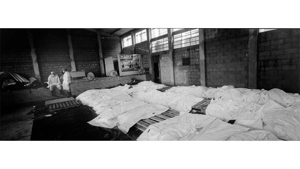 In a makeshift morgue, dozens of victims' bodies wrapped in white bags formed a kind of silent corridor that ended with two exhausted forensic doctors taking a break after days and nights of continuous work. (Rodrigo Abd / AP)