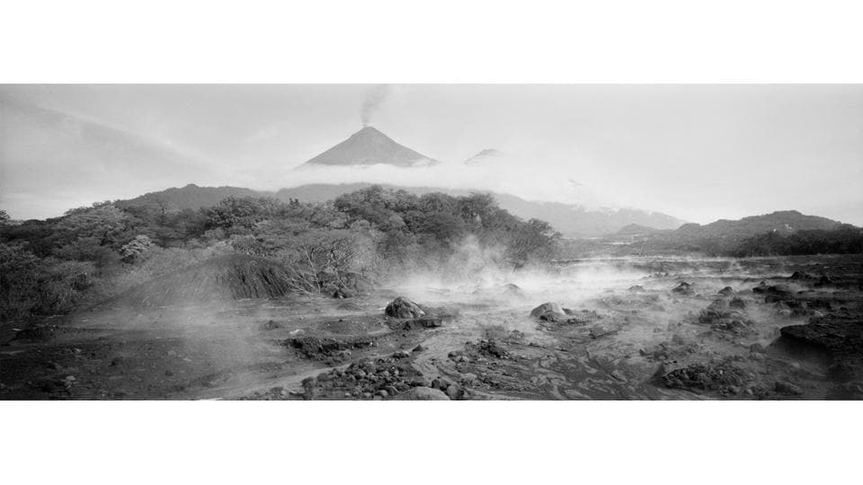 Steam rises from the terrain in San Miguel Los Lotes, Guatemala devastated by an eruption of the Volcano de Fuego, pictured in the background. On June 3, the mountain erupted with a fury not seen in more than a century, exploding with 1,300-degree molten rocks and black clouds of ash that smothered villages and buried at least 194 people alive. (Rodrigo Abd / AP)