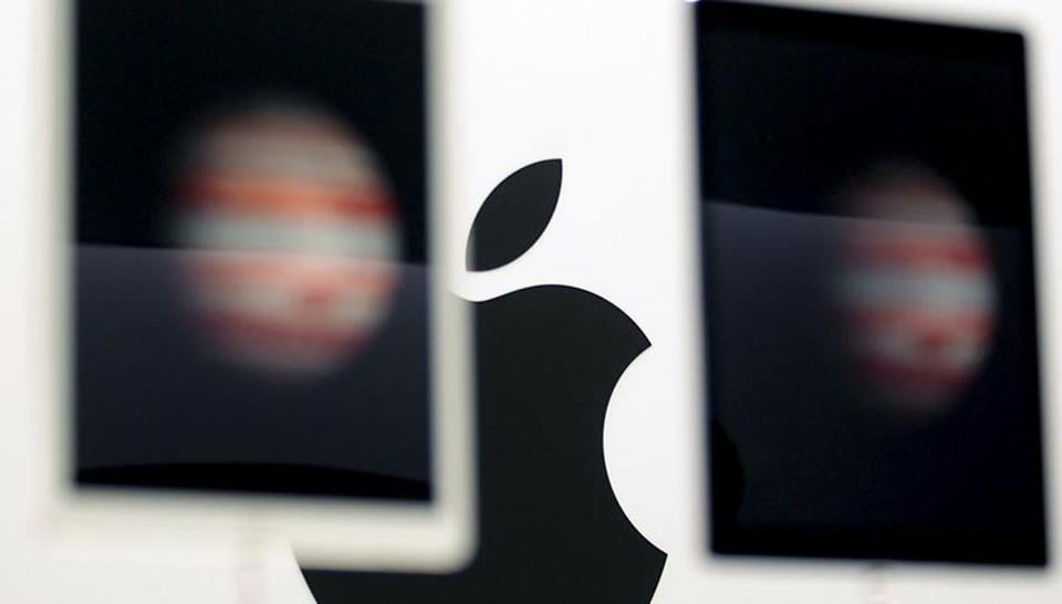 The Apple logo is seen behind new Apple iPad Pros on display during an Apple media event in San Francisco. Photo: Reuters