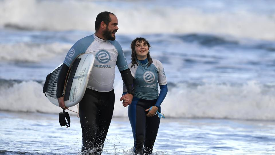 "Garcia, who swims next to Lopez when she surfs, is her 'eyes' when it comes to telling her about a wave coming up. ""A single whistle means the wave is coming on her right side, and a double whistle, on her left side,"" he said, likening the signals to the way dolphins communicate. (Eloy Alonso / REUTERS)"