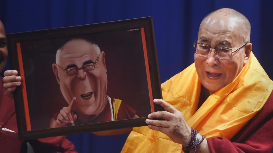 Spiritual leader Dalai Lama gestures as he holds a caricature during the 11th Silver Lecture Series, where the 83-year-old leader spoke on 'The Compassion and the Need for Universal Responsibility', at Guru Nanak College in Mumbai. (Shashank Parade / PTI)