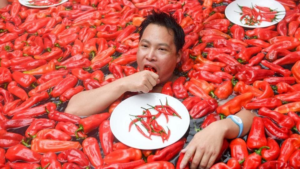 A competitor takes part in a chilli pepper eating contest in a hot spring filled with chilli peppers in the Mingyue Qiangu Scenic Area in Wentang Town, Jiangxi, China. The winner took one minute to eat 20 peppers. (Stringer / AFP)