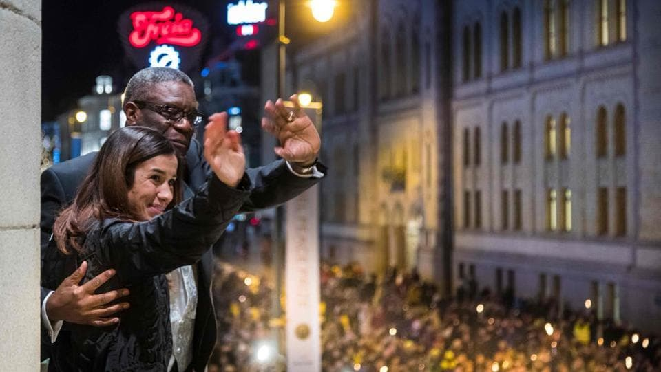 Nobel prize laureates Congolese gynecologist Denis Mukwege (L) and Iraqi Yazidi-Kurdish human rights activist Nadia Murad wave to people holding candles during a torchlight procession in their honour, in Oslo downtown, Norway. (Heiko Junge / NTB Scanpix / AFP)