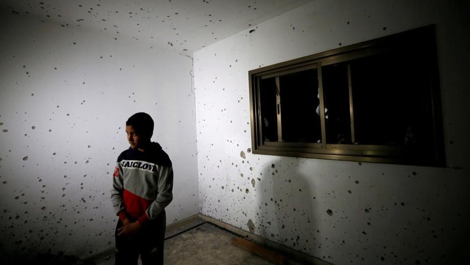 A boy looks on as he stands in a damaged house where a Palestinian gunman was killed by Israeli forces, near Nablus in the Israel-occupied West Bank. (Abed Omar Qusini / REUTERS)