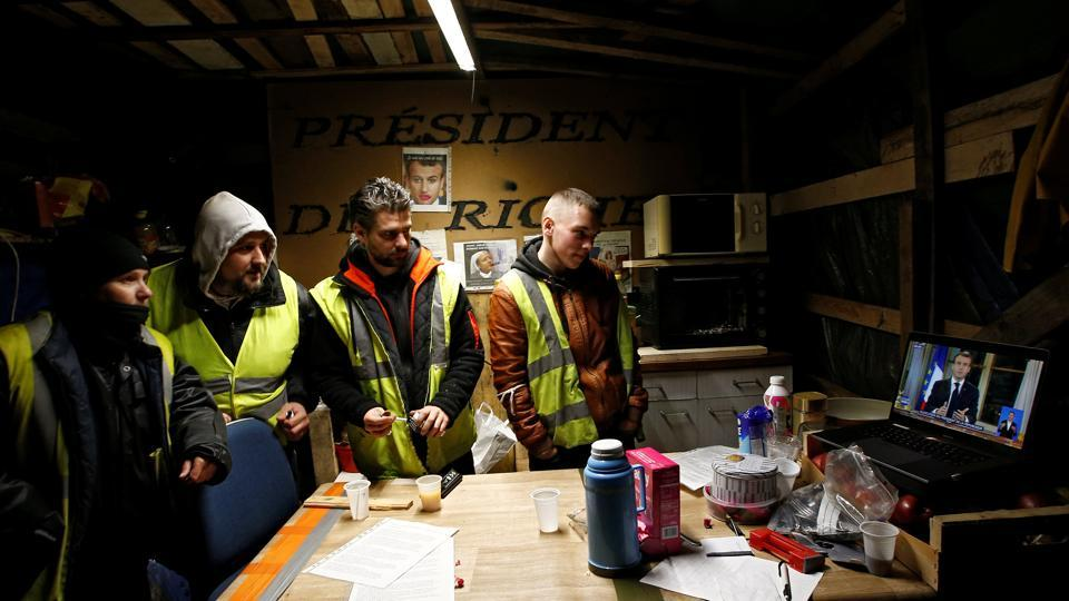 Protesters wearing yellow vests watch French President Emmanuel Macron on a TV screen in Bouguenais, France. Macron's 13-minute address over the protests and economic disparity failed to quell the yellow vests. (Stephane Mahe / REUTERS)
