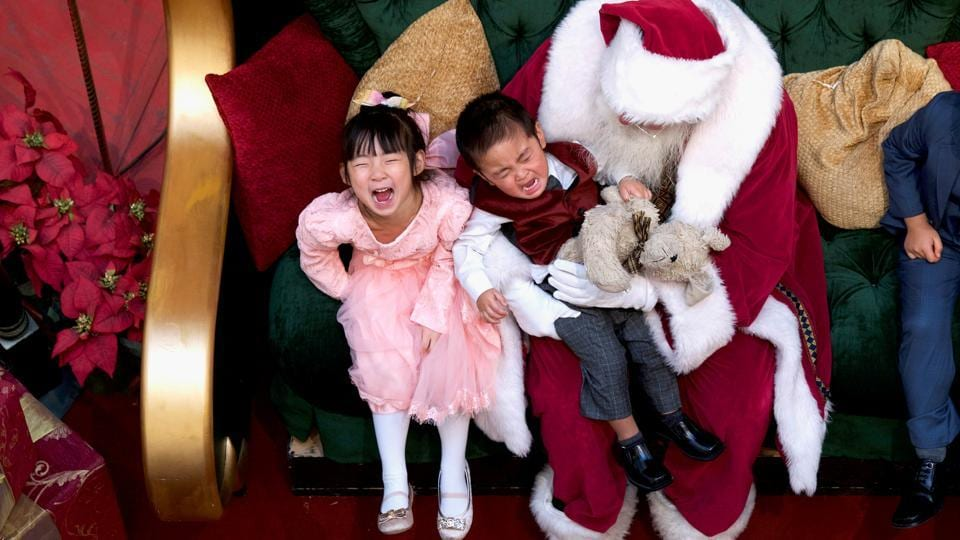 A girl laughs while her brother cries while being held by Santa Claus at the King of Prussia Mall, in Pennsylvania. (Mark Makela / REUTERS)