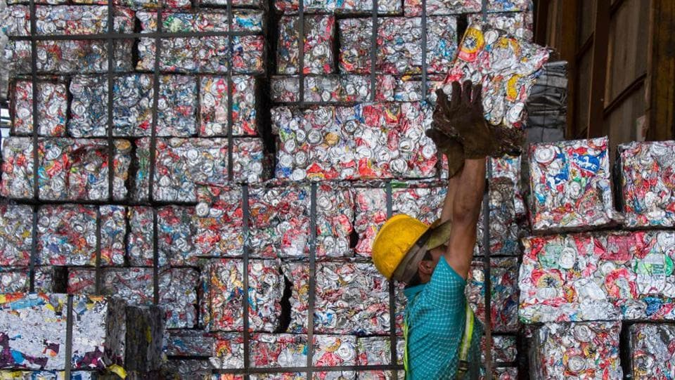 A worker piles recycled tin 'bricks' at La Sylvia recycling centre in Barva, province of Heredia, Costa Rica. The country discards 564 tons of plastic per day of which only 14 are recycled. Since April, a program seeks to stimulate recycling by giving value to waste through the exchange of it for a virtual currency that allows users to make purchases at partner stores. (Ezequiel Becerra / AFP)