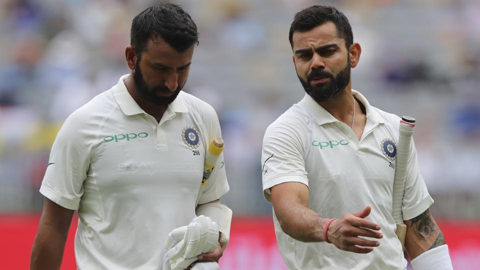 India's Cheteshwar Pujara, left, and Virat Kohli talk as they leave the ground for the tea break. (AP)