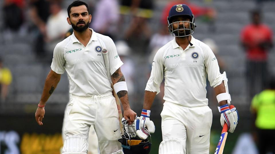 India's batsmen Ajinkya Rahane (R) and Virat Kohli walk back to the dressing room at the end of day two.