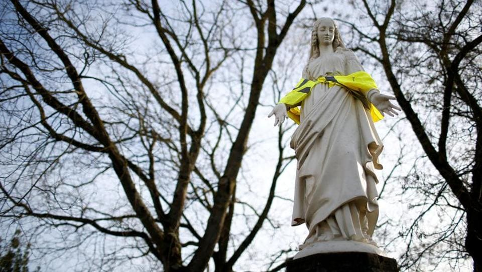 A statue of the Virgin Mary wears a yellow hazard vest in a street in Nantes, France. (Stephane Mahe / REUTERS)