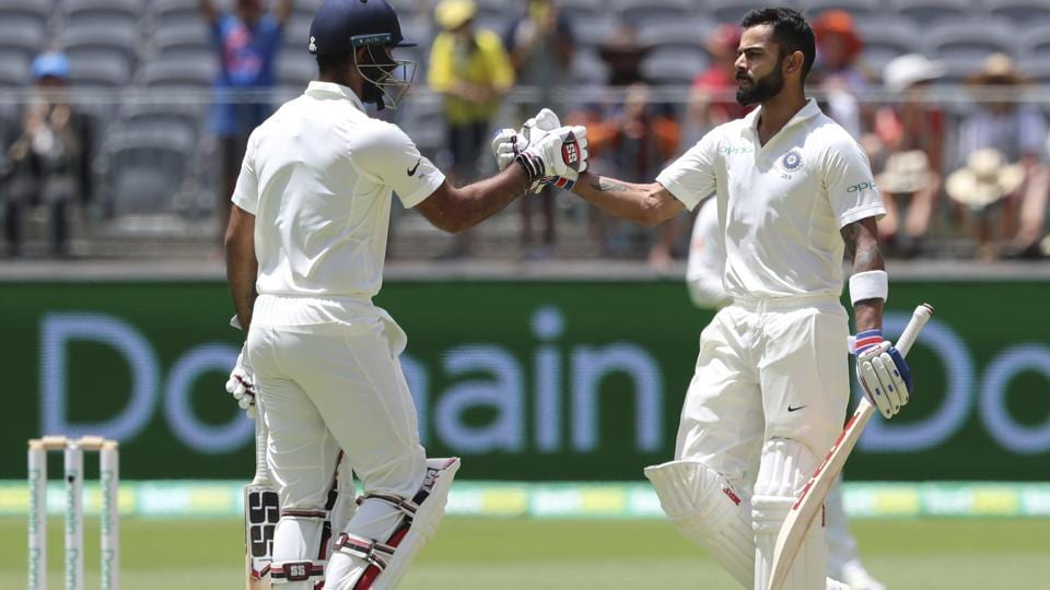 India's Virat Kohli, right, is congratulated by team mate Hanuma Vihari after Kohli scored a century during the second cricket test between Australia and India in Perth (AP)
