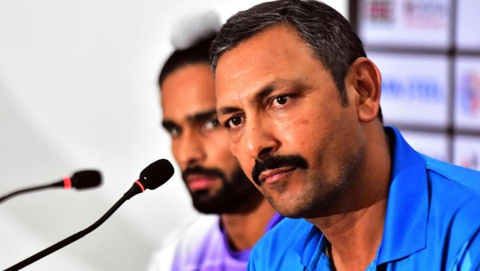 India's field hockey coach Harendra Singh (R) speaks next to player Akashdeep Singh (L) during a press conference.