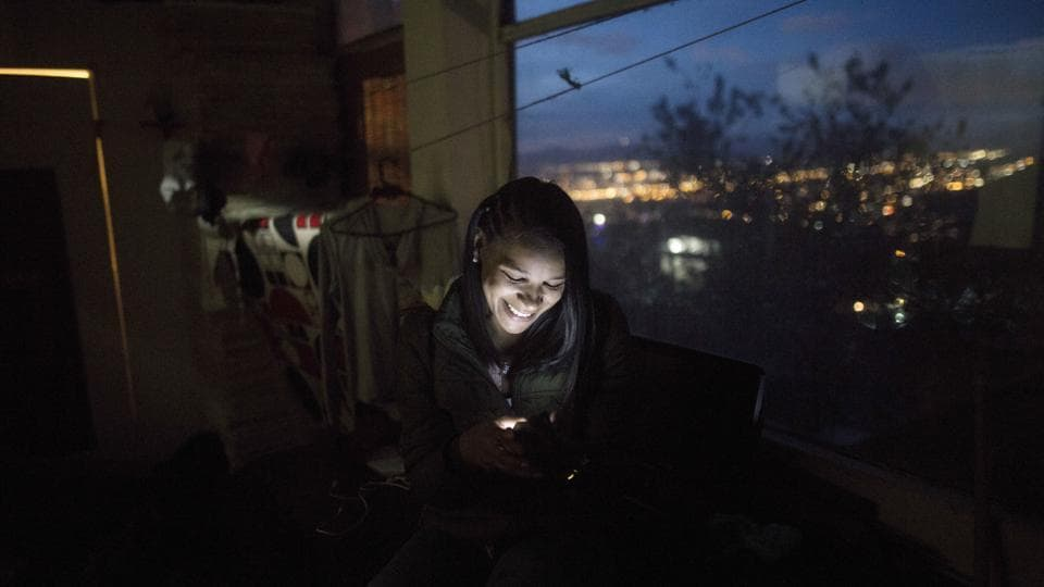 Emili Espinoza smiles during a video call with her children, in Bogota, Colombia. When Espinoza finally spoke to the 3-year-old son she hadn't seen since fleeing Venezuela, little Elvis didn't recognize her. His cold denial sent a shiver of sadness down her spine, overtaking joy. She reminded him of the chocolate-covered bananas she used to buy him, hoping to trigger a memory. But his young mind couldn't grasp the recollection. (Ivan Valencia / AP)
