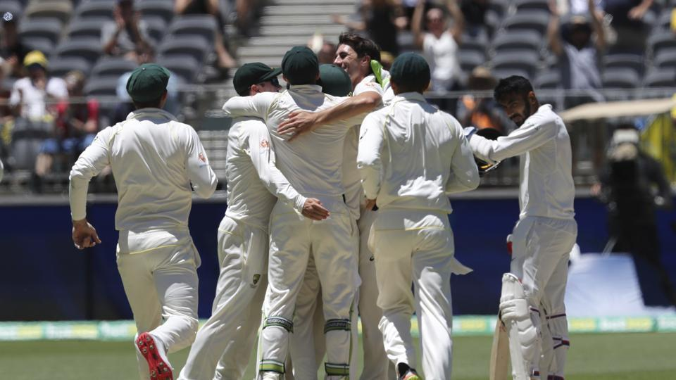 Australian players celebrate winning the test match as India's Jasprit Bumrah, right, looks on at the conclusion of the second cricket test between Australia and India in Perth. (AP)