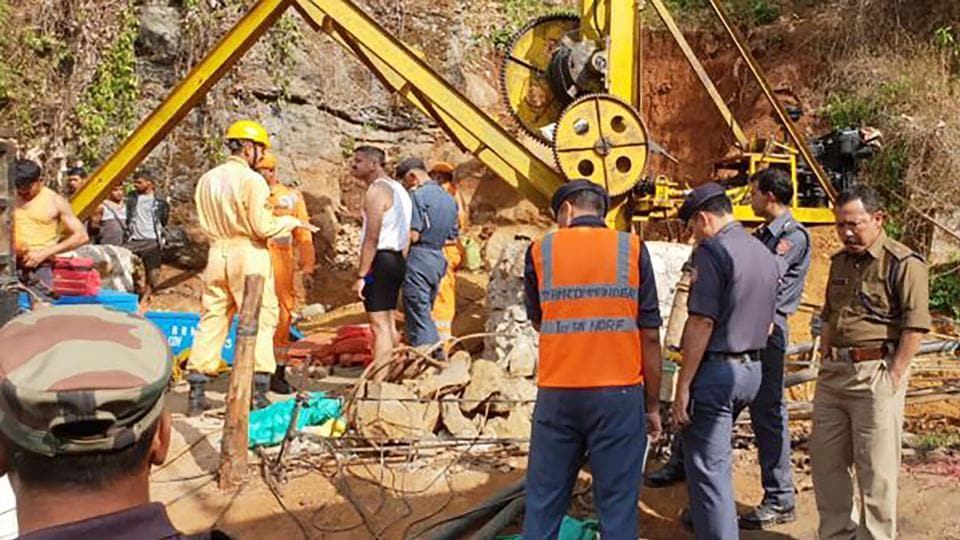 Emergency workers gathering around a crane after 13 miners were feared killed after being trapped by flooding in an illegal coal mine in Ksan village in Meghalaya's East Jaintia Hills district.