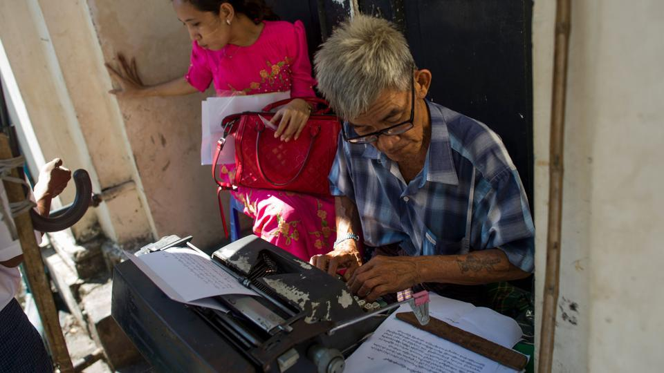 Aung Min, 72, a trained typist in the military types on a customer's document. After he retired in 1980 he has been working on Pansodan ever since. Based outside the High Court, Aung Min specialises in legal documents, from marriage certificates to notarised letters. Although living costs have increased over the years, he struggles to make more than 5,000 kyat ($3) a day -- a sign that Myanmar's transition is passing some people by. (Ye Aung Thu / AFP)