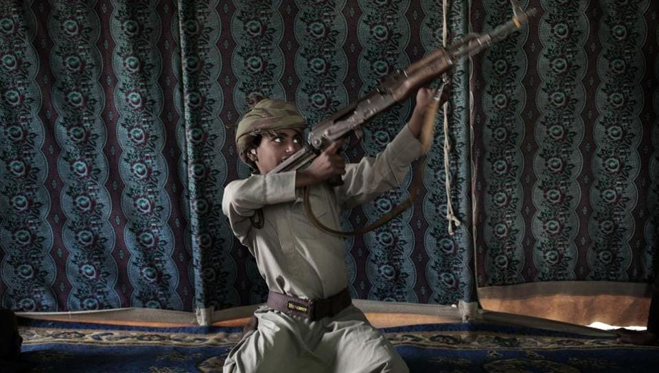 "Kahlan, a 12-year-old former child soldier, demonstrates how to use a weapon, at a camp for displaced persons where he took shelter with his family, in Marib, Yemen. Houthi rebels took Kahlan and his classmates, promising school bags, but instead enlisted and trained them as fighters eluding explosions and airstrikes on the front lines. ""The sight of the bodies was scary,"" he said. (Nariman El-Mofty / AP)"