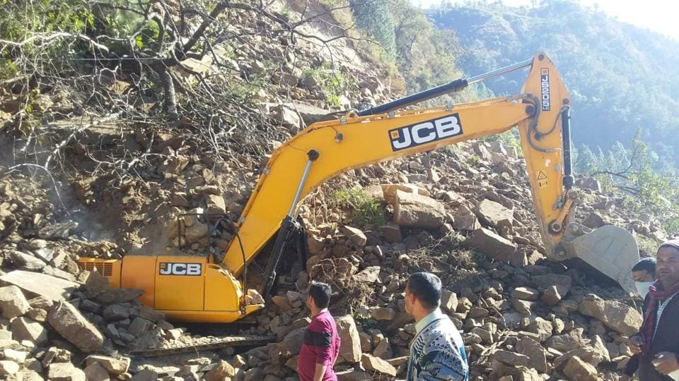 An earth-moving machine at the site of a landslide, which left at least seven labourers dead, in Uttarkhand's Rudraprayag district