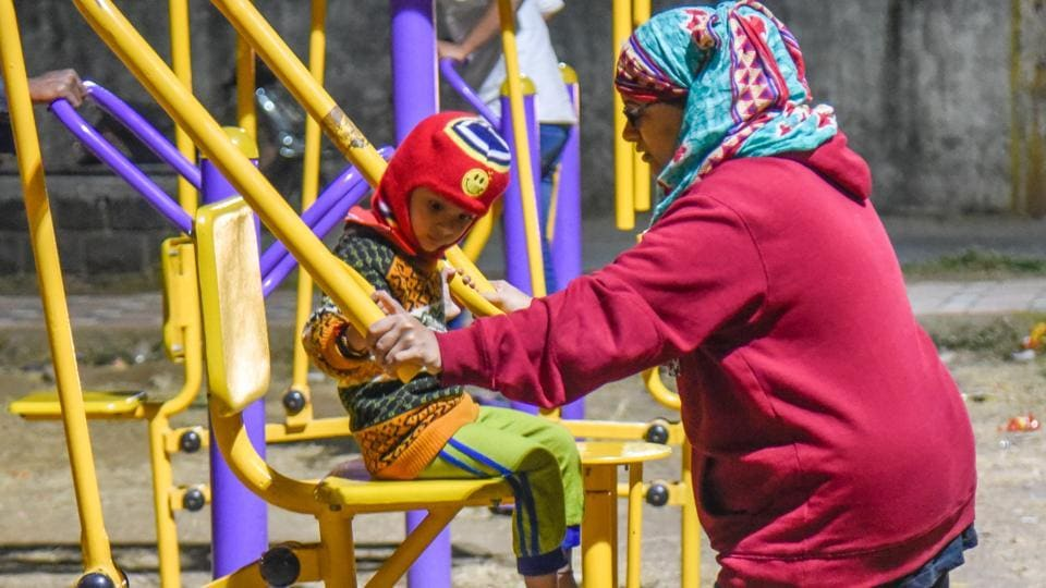 A mother-son duo covered in warm clothes at the open gym at Jeet ground in Kothrud on Thursday. (SANKET WANKHADE/HT PHOTO)